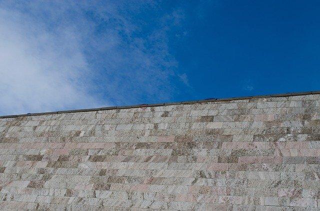 Pohled zdola na betonový plot s cihlovým designem